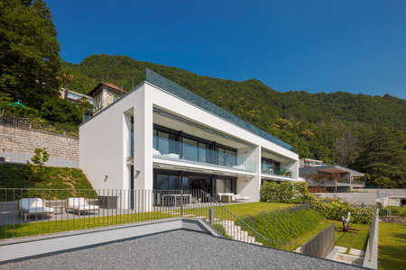 Modern house of two apartments with a beautiful garden directly on Lake Ceresio. Sunny day with blue sky. Minimalist and linear architecture. Panoramic view in background of green hills during summer day.