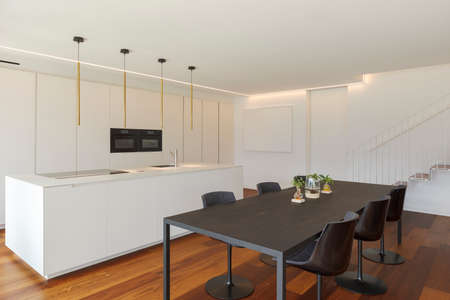 Interior of a modern apartment, kitchen and dining room stand together. The floors are in a luxury and very precious parquet, the kitchen is white. In short, a super design architecture. Standard-Bild
