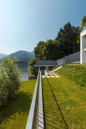 Exterior of a modern house, the garden overlooks the lake. A landscape that gives a feeling of bliss. Nobody inside