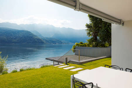 Private terrace overlooking Lake Ceresio in Switzerland. In front of a beautiful green lawn table and chairs. It's a sunny day and it's midsummer