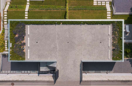 Top view of modern house with garden. There is a parking lot with lavender on the roof. The grass is green. No person inside