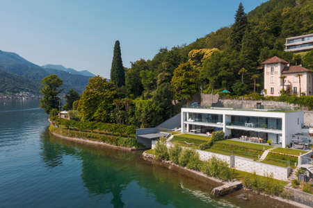 Modern house with direct access to the lake. Aerial drone view from the lake of the house and the landscape surrounding the house. Want to relax and summer.