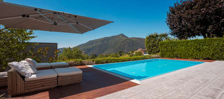 Large modern pool with two sun loungers for sunbathing and an open umbrella. View of the mountains of Switzerland. Nobody inside.