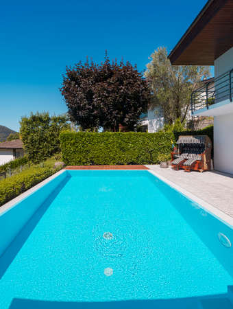 Front view pool with clear water and large green hedge, perfect for a vacation. Sunny day with blue skies and nobody inside. Standard-Bild