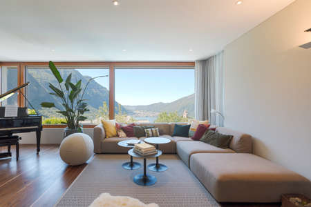 Front view of a living room with large, light-colored sofa and lots of pillows. Large window to the valley with lake view. Nobody inside