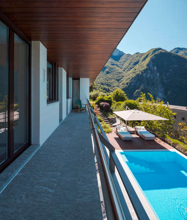 Balcony of villa with rock floor and wooden ceiling. Downstairs you can see the pool perfect for a swim. View of the green mountains of Switzerland. Nobody inside Standard-Bild