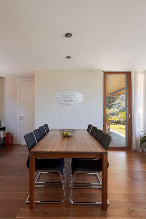 Front view dining room with wood table, leather chairs and dark hardwood floors. Stylish modern home. Nobody inside