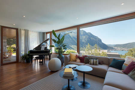 Living room with large light-colored sofa and lots of cushions and a black piano. Large window overlooking the valley with a lake view. Nobody inside