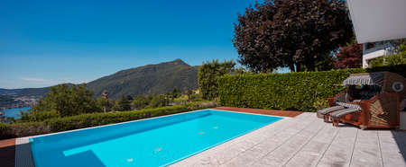 Large modern pool overlooking the lake and valley, nestled in the mountains of Switzerland. Sunny day, perfect for a vacation. Nobody inside