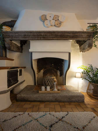 Front view of a fireplace in the living room of a mountain house. Tiles and a carpet on the floor. Nobody inside Standard-Bild
