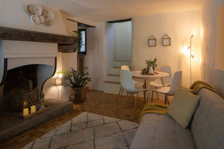 Modern living room of a mountain house with a table, four designer chairs and a comfortable sofa with a blanket. Nobody inside Standard-Bild