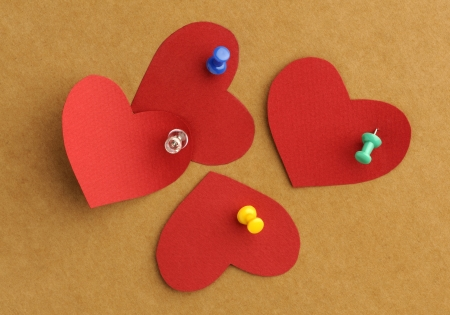 Red papers hearts with the thumbtacks on the board photo
