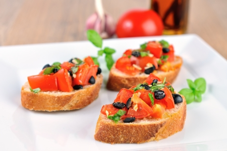 hot bruschetta on wooden table and white plate closeup photo