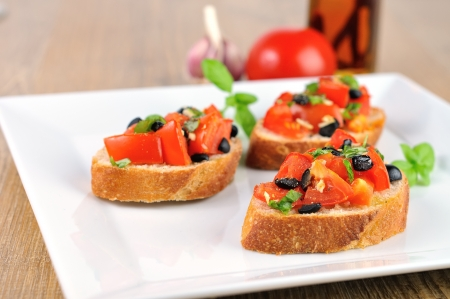 tasty bruschetta on wooden table and white plate with chilioil photo