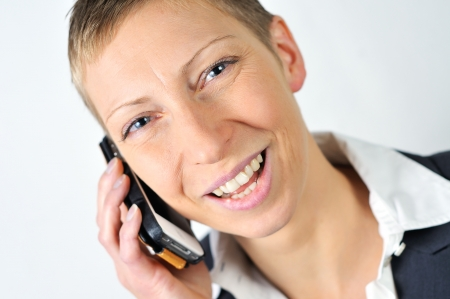 blonde businesswoman with a mobile is laughing photo