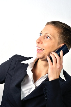 blonde businesswoman with a phone is calling and white background photo