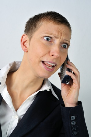 annoyed blonde businesswoman with a phone is calling  photo