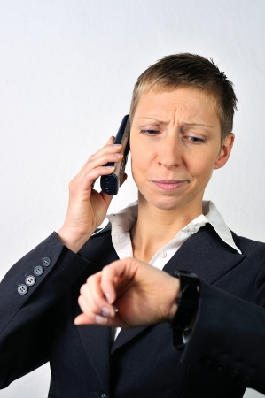 desperate blonde businesswoman with a phone is calling  photo
