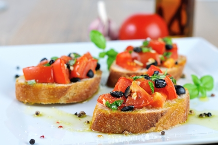 tasty bruschetta with oil on wooden table and white plate close up photo