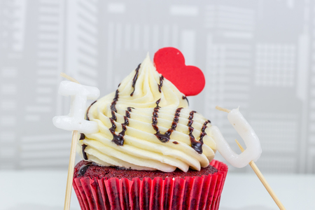 Red cupcakes with cream on top and heart-shaped sugar. Stock Photo