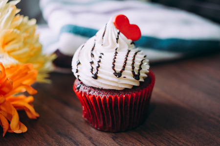 Red cupcakes with cream on top and heart-shaped sugar placed on the table near the window in the morning, vintage tone. Zdjęcie Seryjne