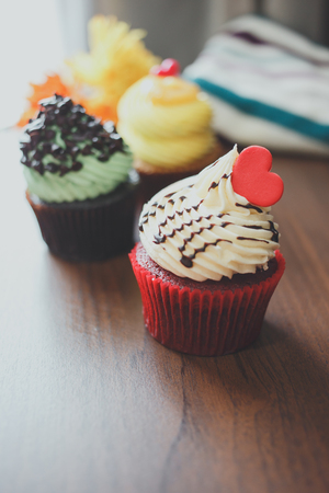 Three cupcakes of yellow, red, and green are arranged on table.