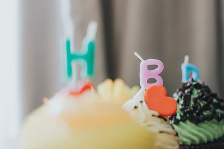 Three cupcakes of yellow, red, and green are arranged horizontally with the letter H B D, Happy Birthday