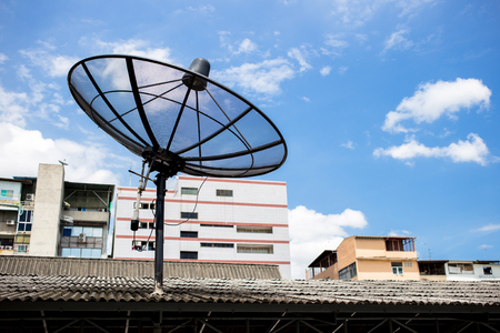 A satellite dish on the roof with a building and sky background. Zdjęcie Seryjne