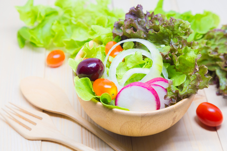 Salad in a wooden bowl on a wooden table, lettuce, tomatoes, cherries.