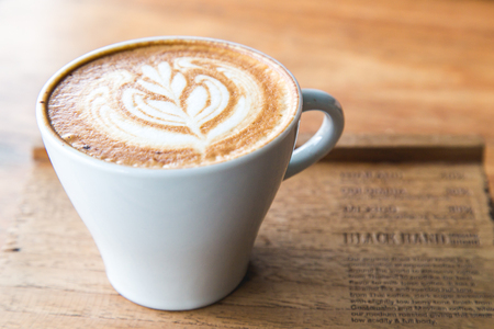 Cappuccino in white glass with wire drawing on milk froth.