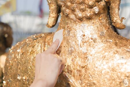 Stick gold sheet on Buddha statue. Religious ceremony of Thailand.
