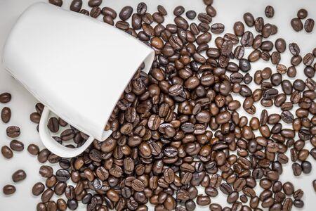 Coffee beans spilled from white ceramic cup. Zdjęcie Seryjne