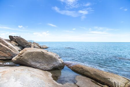 Beautiful landscape blue sky sea and waves on beach near the rocks during summer.