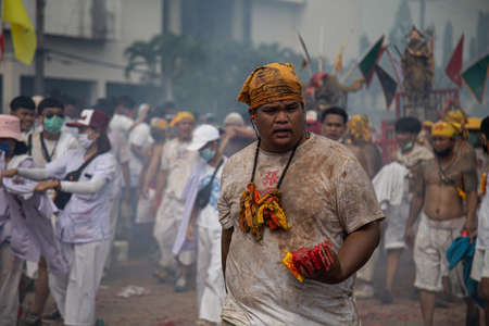 group of men march in the middle of firecrackers and smoke at a vegetarian festival, Phuket, Thailand, on October 5, 2019.