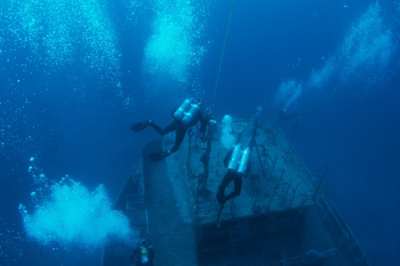 Scuba divers descending on an artificial reef in south east Florida. 免版税图像
