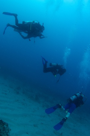 Scuba Divers swimming over a sandy bottom in south east Florida. Stock Photo