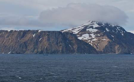 Fishing boat dwarfed by the a large mountainous Aleutian Island. Stock Photo