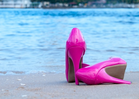 Pair of pink high heels on the beach