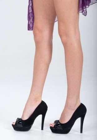 tacones negros: Parcial de un womans piernas con zapatos de tac�n negro sexy. Foto de archivo