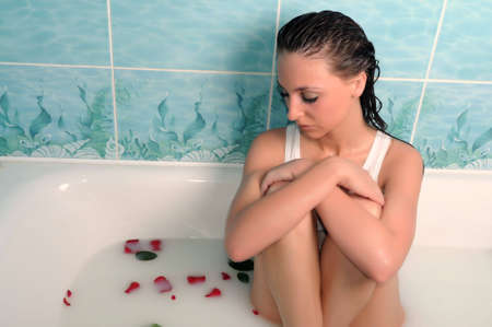 The beautiful woman sits in a bathroom with rose-petals