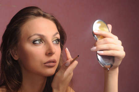 A beautiful young woman applying her make-up in the mirror photo