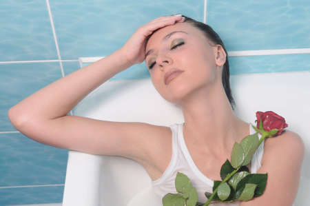 Gorgeous brunette with flower. In a bathroom photo