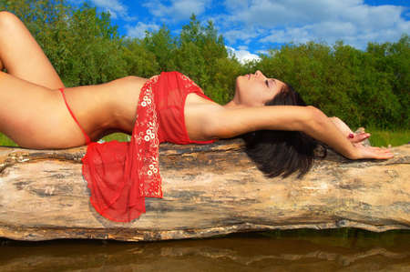 Image of relaxing woman in red, lying on the tree