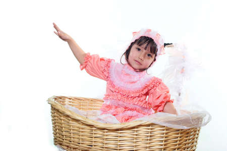 The little girl sits in a basket with the lifted hand Stock Photo