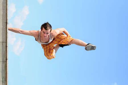 man dances a break-dance against the sky