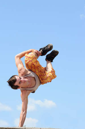 breakdance style dancer doing freeze position in the sky