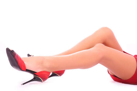 Sexual long feet of the girl in a red dress and shoes Stock Photo - 5232740