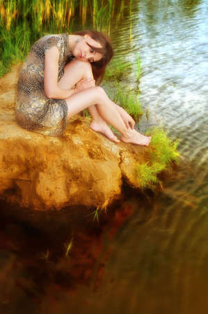thoughtful and sad woman sits near water