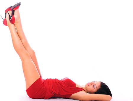 young woman in a red dress lays on a white background and looks at shoes Stock Photo