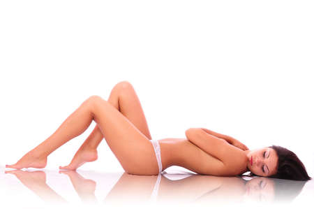 The beautiful woman with reflexion lays on a white background. It is not isolated.